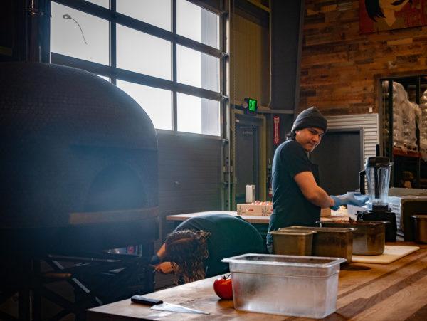 Deux personnes se tiennent derrière une table pour préparer la nourriture.