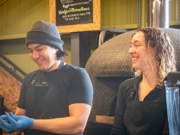 Two people stand in front of a pizza oven, smiling.