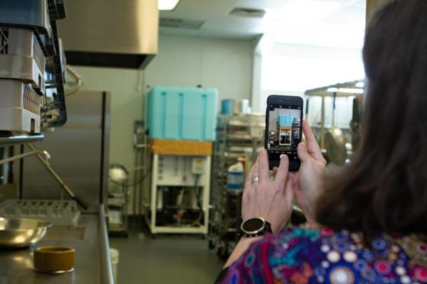 A woman holds a phone up taking  apicture of a big blue tank inside a room