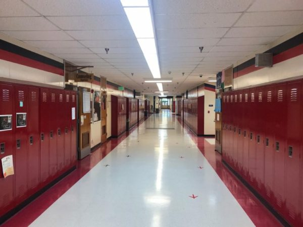 An empty hallway lined with red lockers.