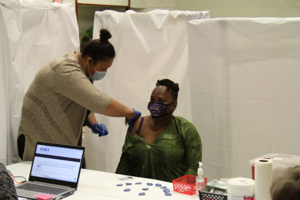 A black woman get vaccinated in her arm by a Hawaiian nurse