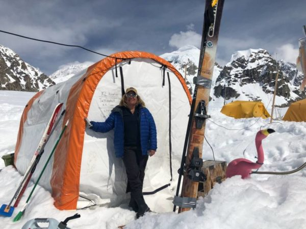 A woman stands outside a tent in a snowy area