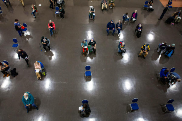 As seen from above, people sit in chairs spaced six feet apart