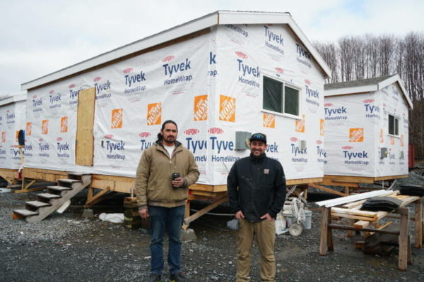 Two men in work clothes stand in front of a tyvek home