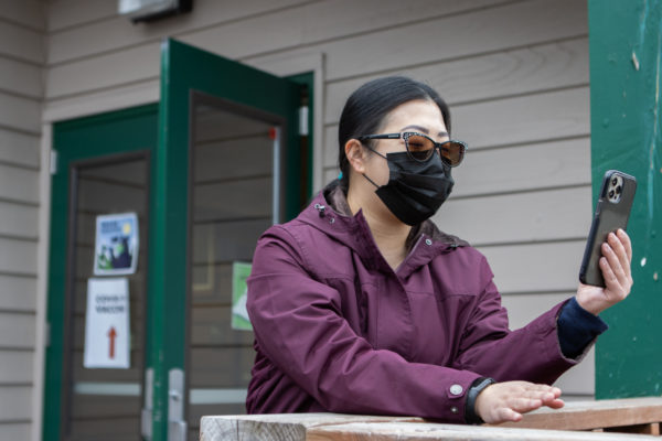 woman with mask on looks at phone screen