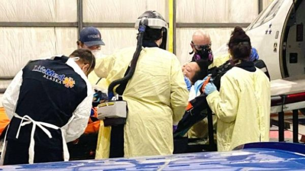 A woman surrounded by medical professionals inn PPE on a stretcher by a plane
