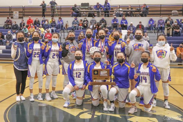 A girls  basketball team poses for a photo holding up their pointer fingers in a #1 sign while one girl kneels and holds a championship plaque