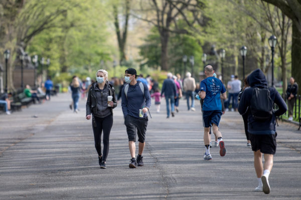 NEW YORK, NEW YORK - APRIL 25: Two people wearing masks  avoid social distancing in Central Park as temperatures rose amid the coronavirus pandemic on April 25, 2020 in New York City, United States. COVID-19 has spread to most countries around the world, claiming over 200,000 lives with over 2.8 million cases.  (Photo by Alexi Rosenfeld/Getty Images)
