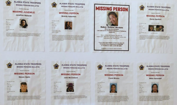 Eight missing person's posters on a bulletin board.