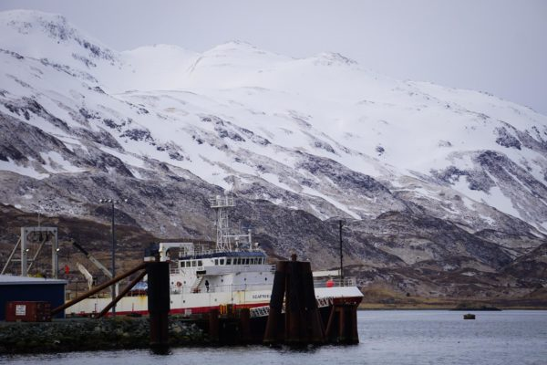 A boat at dock in front of a snow-covered montain