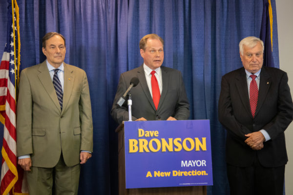 mayor elect speaks at a podium with two men next to him