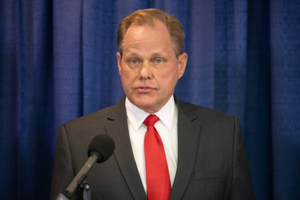 man with red tie speaks at a podium