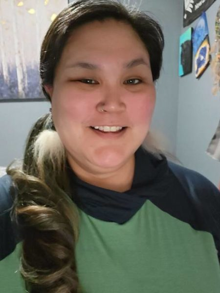 A woman in a green and navy blue shirt smiles for a photo.