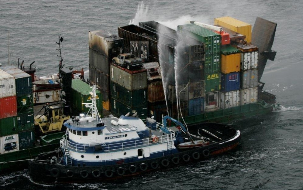 A boat with hoses spraying a bunch of conexes on a barge