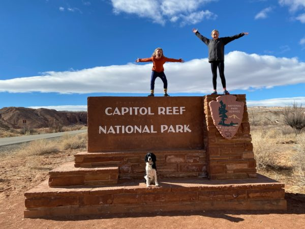two children stand on a national park sign