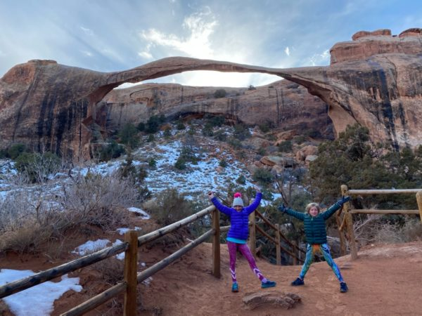 two children stand in front of a rock arch