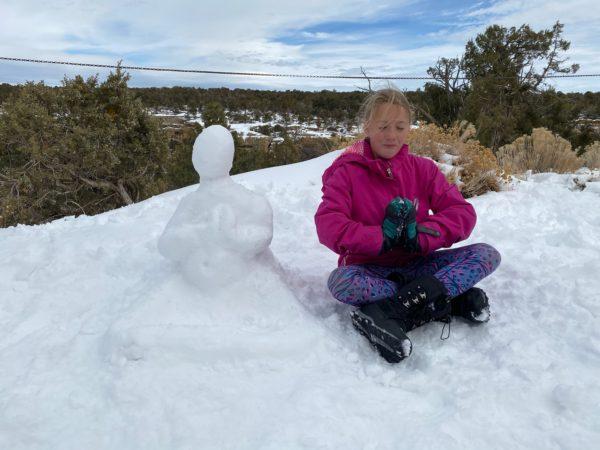 a girl sitting with a snowman buddha