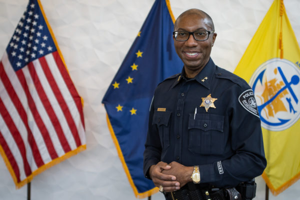 A man in a police uniform smiles for a photo in front of flags