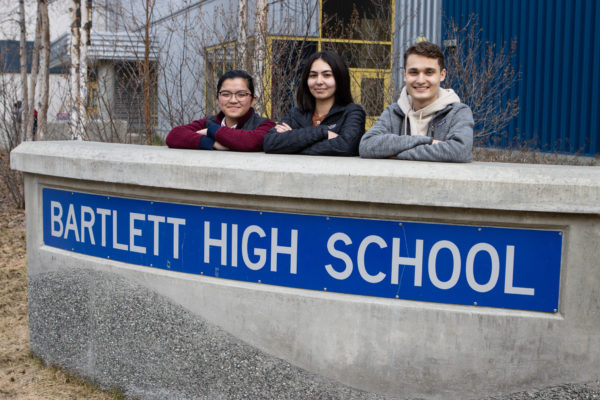 three highschool students pose in front of sign that reads: bartlett high school