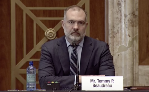 """Man in suit at a microphone. name plate on desk says """"Mr. Tommy P. Beaudreau"""""""