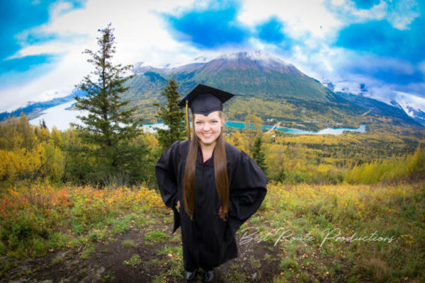 A high school senior in a cap and gown poseses in front of a green mountain