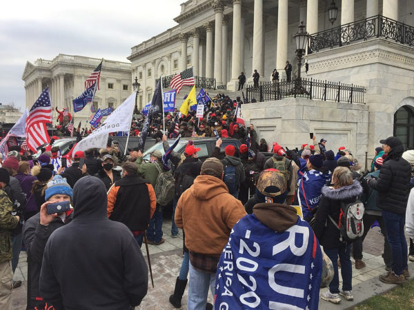 crowd with Trump banners and flags in front of Capitol