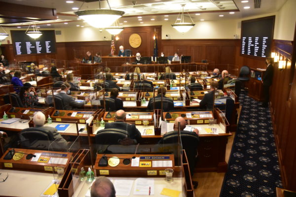 A group of lawmakers sit at desks in a big room. Each of them is behind a Plexiglass shield.