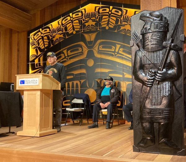 An Alaska Native person speaks at a podium in front of Tlingit motifs