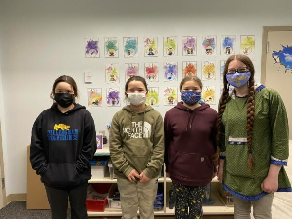 Three young girls and a female teachers stand in a line, posing or a photograph. Each one is wearing a face mask.