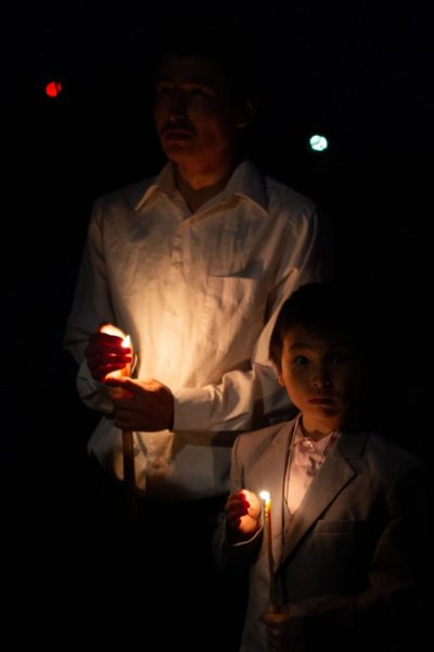 A person holds a candle with a child next to him