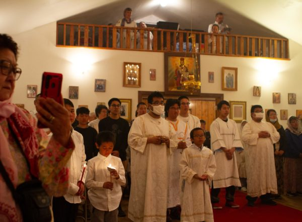 People in white robes inside a church