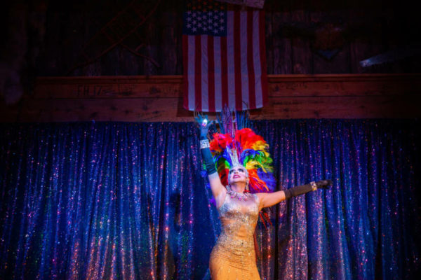 A person in drag stands on stage raising their  hands