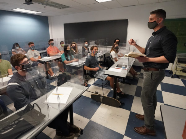 A teacher wearing a face mask, stands in front of a class of students who are also wearing face masks and sitting behind plexiglass shields.