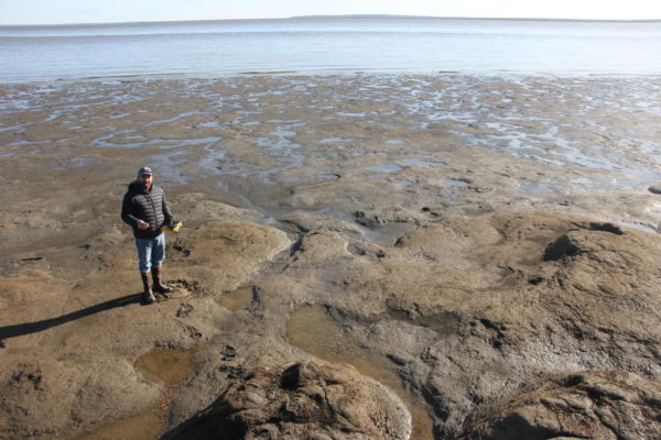 A man in a winter jacket and boots stands on a muddy patch of a swampy lagoon.