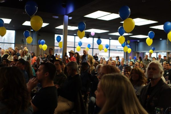 A room filled with people  an blue and yellow baloons