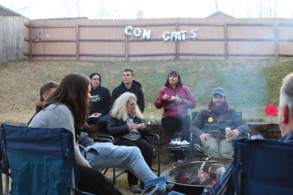 People sit around a bonfire