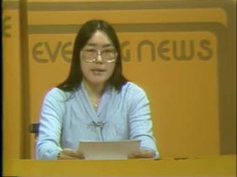 An Alaska Native woman with glasses reads from a paper at a desk