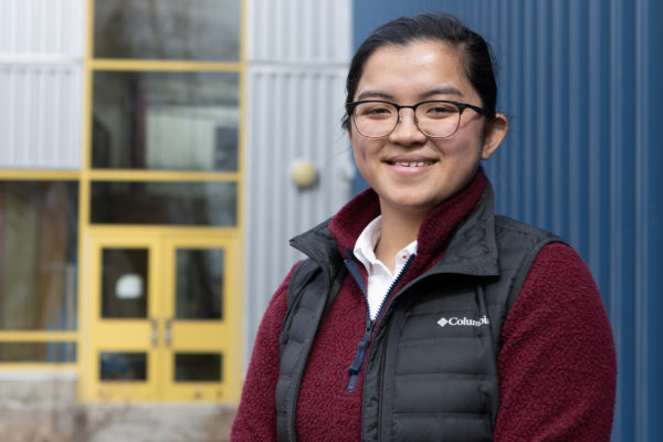 high school girl smiles for photo in front of a building