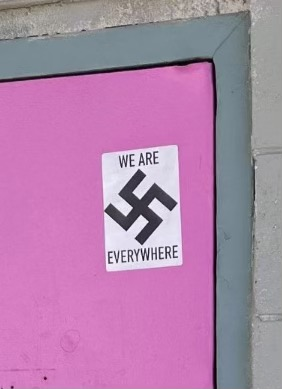 A swastika sticker in the top corner of a pink door