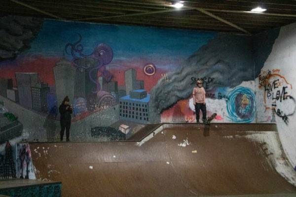 A woman descends a half pipe with graffittti on the wall behind her