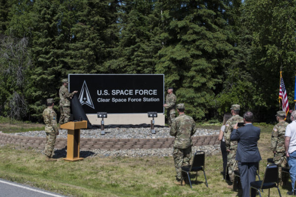 Several people in army unifroms sit in front of a black sign