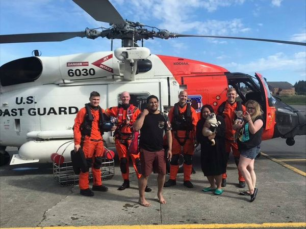 A crew of people pose in front of a coast guard helicopter