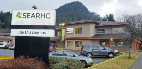 A tan building with a parking lot in front and mountains behind, with a sign in front that says searhc