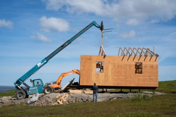 A crane and backhoe put up a house in a green field