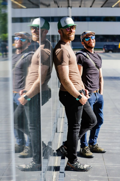 two people pose for a portrait against their mirrored reflection
