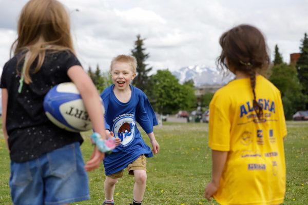 A boy in a blue shirt runs towars a ball