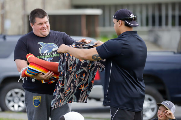 A white man accepts a gift of a blanket