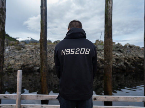 A man with his back turned stands in a dock facing the water. The back of his black sweathshirt has numbers