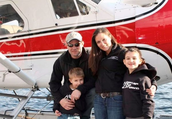 A mother, father, and two young kids pose in front of a red float plane
