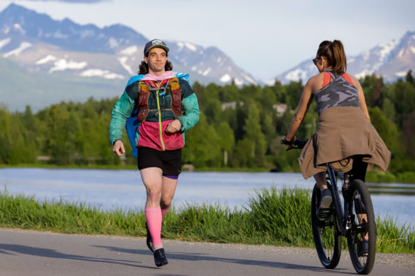 a person wearing sports clothes, high heels and a cape is jogging by a biker in front of a body of water